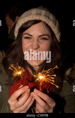 26 year old girl having fun with sparklers on bonfire night, Chiddingfold, Surrey, UK. - Stock Photo