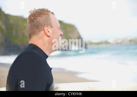 Surfer wearing wet suit on beach - Stock Photo