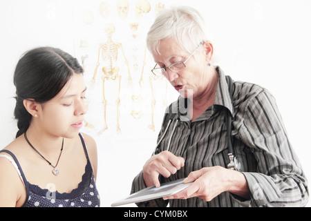 Doctor showing x-ray to teenage girl - Stock Photo