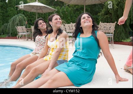 Women dangling feet in swimming pool Stock Photo