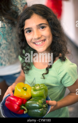 Smiling girl holding bowl of peppers - Stock Photo