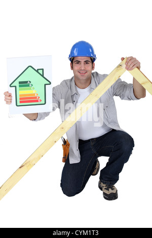 Tradesman holding a frame and an energy efficiency rating chart - Stock Photo