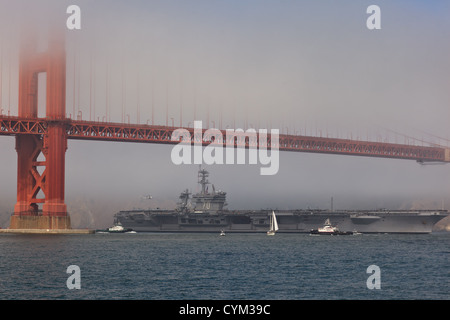 Aircraft carrier USS Carl Vinson passes under the Golden Gate Bridge during Fleet Week celebration accompanied by - Stock Photo