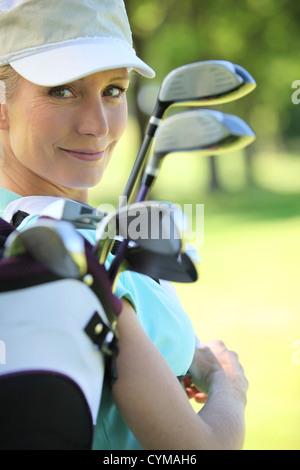 Female golfer carrying golf bag - Stock Photo