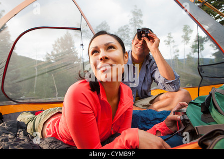 Couple sitting in tent together - Stock Photo