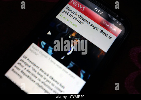 A smartphone screen showing news of President Obama's re-election following the 2012 US election. - Stock Photo