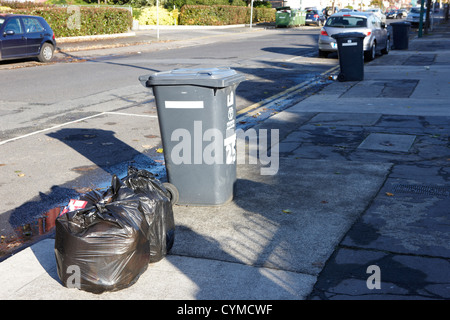 extra plastic bags left beside wheelie bin for kerbside collection dublin republic of ireland - Stock Photo