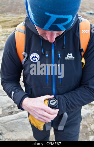 A man using a wrist watch GPS navigation system in the Scottish Mountains - Stock Photo