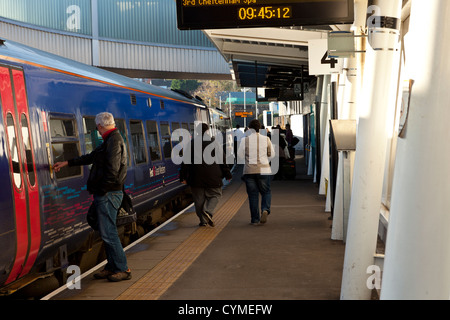 Commuters and passengers boarding a train at Newport railway station. - Stock Photo