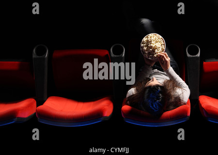 a pretty young woman sitting in a row of red chairs in a theater, she eats popcorn, top view - Stock Photo