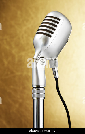 Retro style microphone. Gold background - Stock Photo