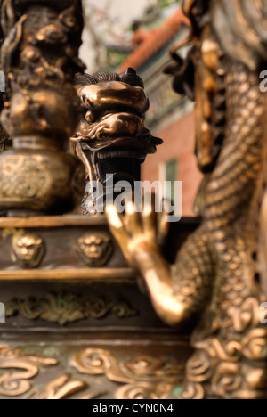 Chinese dragon on traditional incense burner in golden color. - Stock Photo