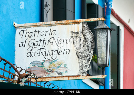 Sign advertising the Trattoria al Gatto Nero da Ruggero, a fish restaurant in Burano, Venice - Stock Photo