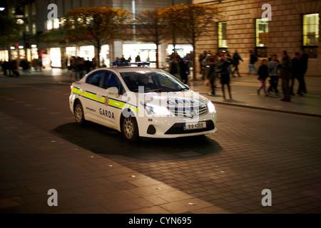 garda siochana patrol car driving along oconnell street at night dublin republic of ireland - Stock Photo