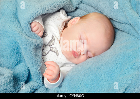 Adorable little baby sleeping peacefully on a blanket - Stock Photo