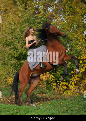 Cowgirl in vintage dress sitting on a rearing horse Stock Photo