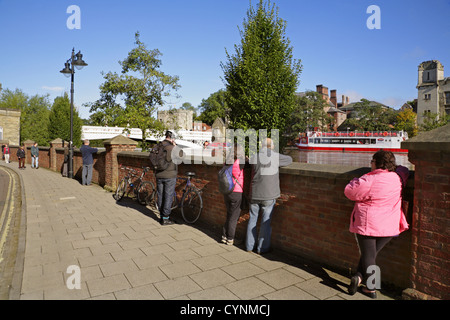 Tourists look over flood defence barriers at the flooded River Ouse, York, and the historic Guildhall. - Stock Photo