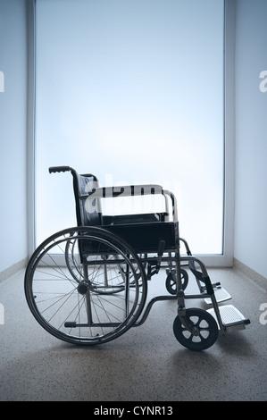Empty wheelchair parked in hospital hallway - Stock Photo