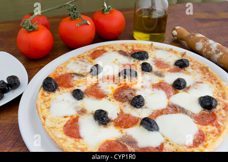 pizza with olives, pepperoni and anchovies - Stock Photo