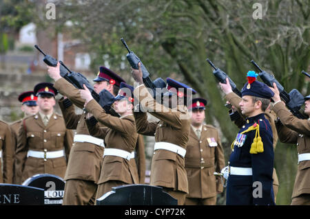 Soldiers fire guns in salute during a military funeral - Stock Photo