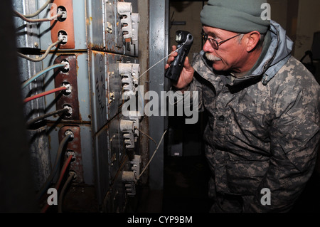 Sgt. 1st Class Marty Newman, of the W.Va. Army National Guard's 3664th Maintenance Company, inspects damaged electrical - Stock Photo