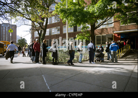 Voters on line outside of a polling location in Chelsea in New York to cast their ballots on election day - Stock Photo