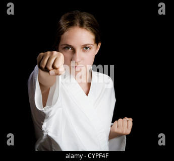 Pretty young girl in karate pose on black background - Stock Photo