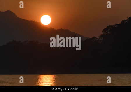 LUANG PRABANG, Laos - Just moments before the sun disappears behind a mountain on the horizon at sunset on the Mekong - Stock Photo