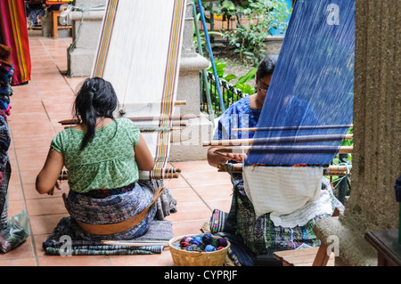 A woman weaving with a traditional backstrap loom in San Antonio Aguas Calientes near Antigua, Guatemala. - Stock Photo