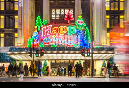 London UK. Christmas shoppers Xmas shopping at Selfridge's store Oxford Street with large neon sign lights Happy - Stock Photo