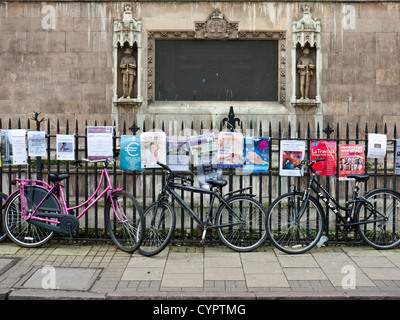 Bikes leaning against the fence outside of Great St. Mary's Church, Cambridge - Stock Photo
