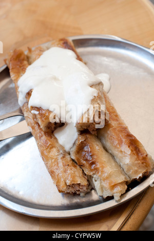 Burek at a restaurant in Sarajevo. Burek is a traditional flaky pastry filled with meat and topped with sour cream. - Stock Photo