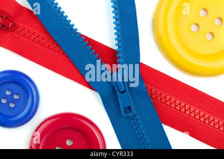 Three colored sewing buttons and two zippers closeup. Isolated on white - Stock Photo