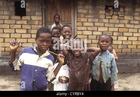 Children pose together for the camera in a typical village setting - Nkhotakota, Lake Malawi, Malawi - Stock Photo