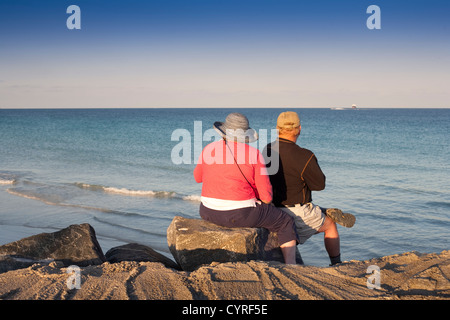 An older couple looking out to sea and enjoying the sunset at Pointe Park Miami South Beach on an afternoon in December - Stock Photo