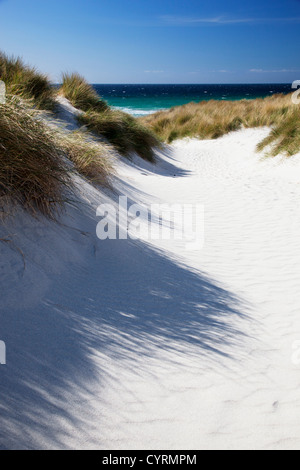 View through the sand dunes at Traigh Eais to the Atlantic Ocean on a sunny day, Isle of Barra, Outer Hebrides, - Stock Photo