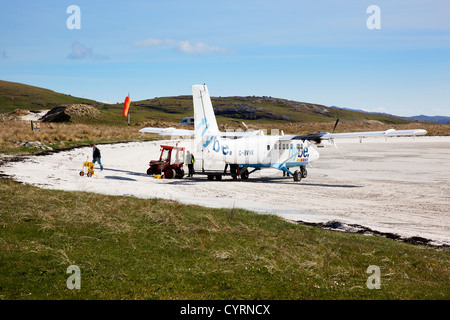 Passengers disembarking and luggage unloaded from flybe flight, Traigh Mhor, Barra, Outer Hebrides, Scotland, UK - Stock Photo