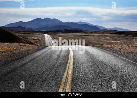 A Two Lane Blacktop Highway Running Through Death Valley National Park, California, USA - Stock Photo
