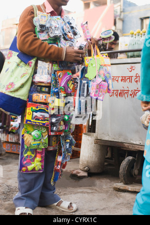 Vendor selling toys in a street market, New Delhi, India - Stock Photo