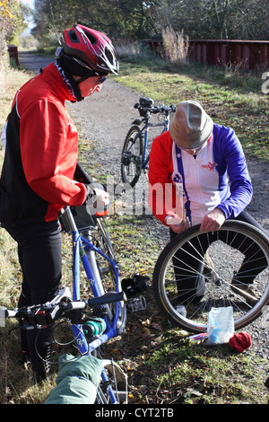 Senior male cyclist repairs puncture as friend holds his bike, coast to coast cycle track near Beamish north east - Stock Photo