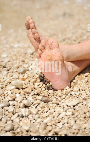 Relaxation on beach, detail of male feet - Stock Photo