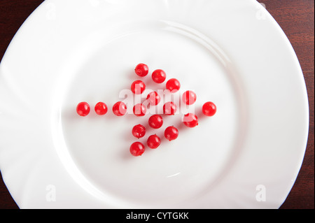 Red arrow from viburnum on white plate - Stock Photo