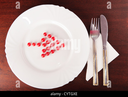 Arrow from red balls on white shows the direction to silverware - Stock Photo