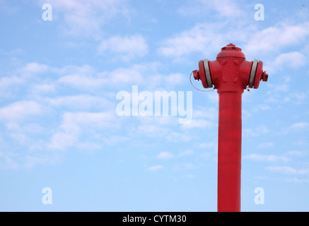 Hydrant, water-hose against blue sky - Stock Photo