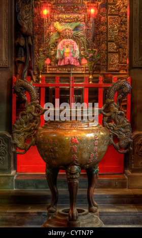 It is an chinese incense burner and god behind. - Stock Photo