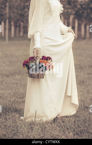 a woman in a victorian dress is walking on a meadow with a basket of flowers - Stock Photo