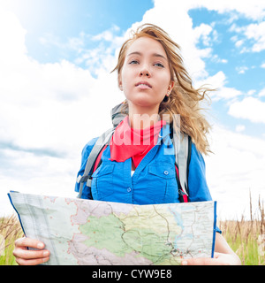 Young pretty woman tourist standing in wheat field with map. Blue cloudy sky in background behind girl. Tourism - Stock Photo
