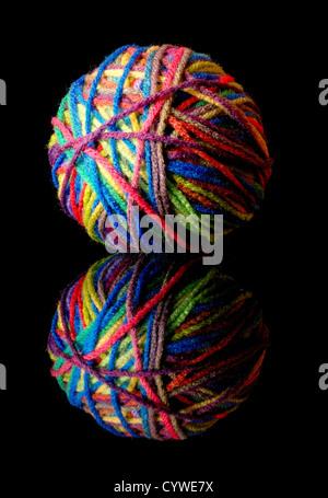 ball of colorful wool yarn on black - Stock Photo