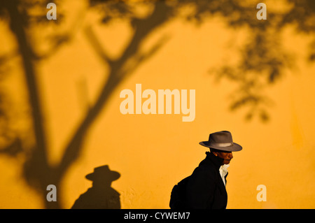 A man walking past a brightly painted yellow stucco wall in Antigua Guatemala casts a strong shadow as he walks - Stock Photo
