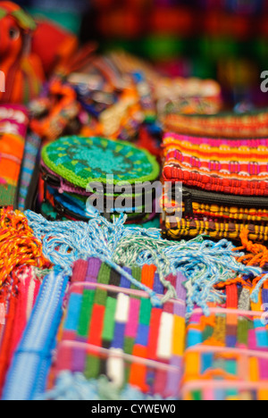 Brightly colored woven textiles are stacked in a market in Antigua Guatemala. Guatemala has a very strong tradition - Stock Photo